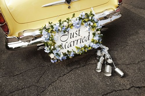 A string of tin cans behind the newlyweds' car